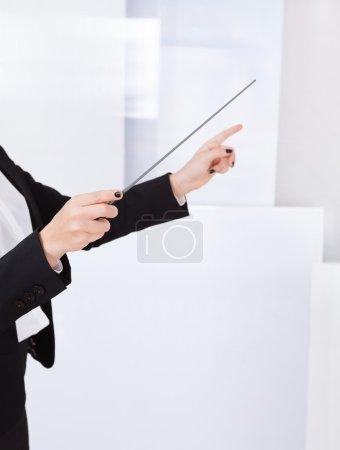 Photo pour Gros plan des mains d'un chef d'orchestre avec une matraque avec fond - image libre de droit