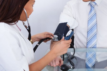 Doctor Checking Businessman's Blood Pressure
