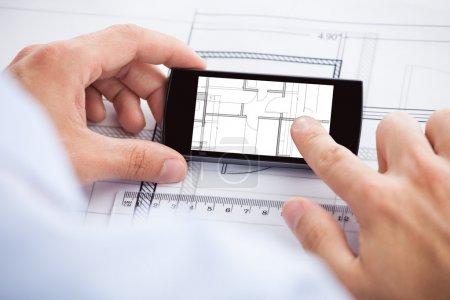 Architect Analyzing Blueprint On Mobilephone