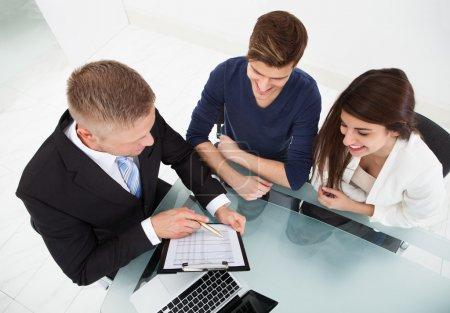 Photo pour Vue de la forte inclinaison du conseiller financier expliquant le plan d'investissement à couple au bureau - image libre de droit