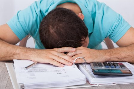 Tired Man With Bills And Calculator At Desk