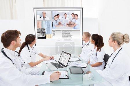 Photo pour Une équipe de médecins examine l'écran du projecteur lors d'une réunion de vidéoconférence à l'hôpital - image libre de droit