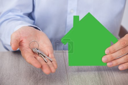 Businessman With Key And Green House Model
