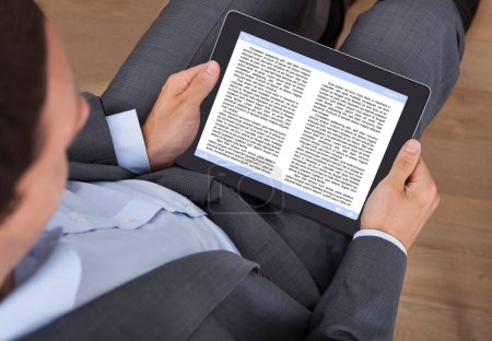 Businessman Reading eBook In Office