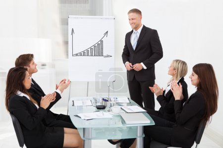 Photo for Young businesspeople clapping for colleague after presentation at desk in office - Royalty Free Image