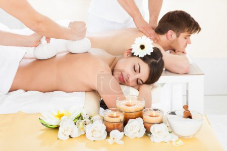 Photo for Cropped image of therapist massaging woman's back with herbal compress stamps at spa - Royalty Free Image
