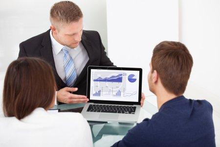Photo pour Conseiller financier expliquant le plan d'investissement de coupler sur ordinateur portable au bureau - image libre de droit
