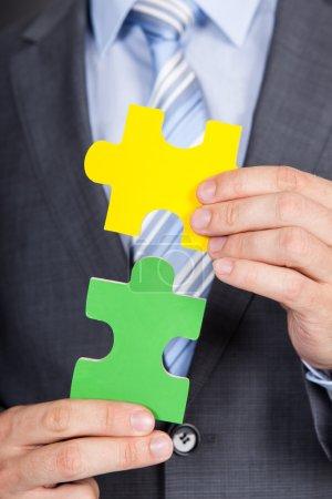 Businessman Joining Jigsaw Pieces
