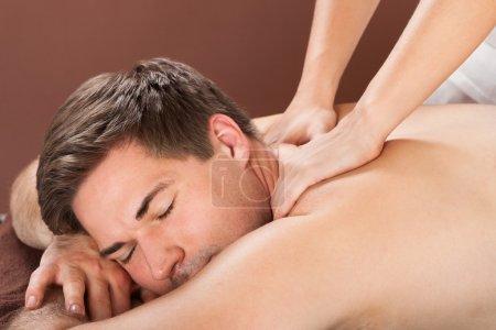 man receiving back massaging in spa
