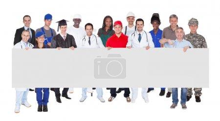 Photo pour Portrait complet de personnes souriantes avec diverses professions tenant le panneau d'affichage vierge sur fond blanc - image libre de droit