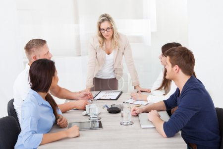 Angry Businesswoman Standing At Desk In Meeting