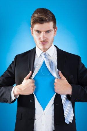 Photo pour Superhéros confiant costume d'homme d'affaires déchirant sur fond bleu - image libre de droit