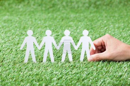 Photo for Man hand holding paper people chain silhouettes on grass - Royalty Free Image
