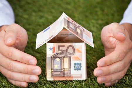 Photo pour Homme d'affaires mains protégeant maison faite de billets en euros sur des terres herbeuses - image libre de droit