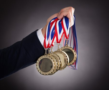 Businessman Holding Gold Medals