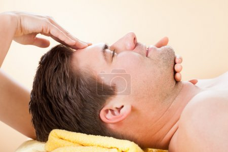 man receiving forehead massage in spa