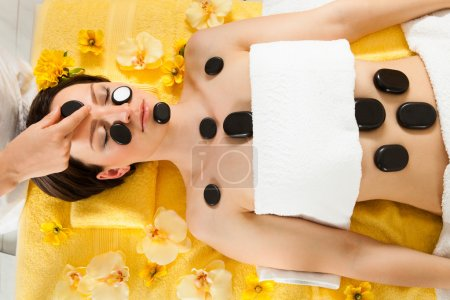 Relaxed Woman Receiving Hot Stone Therapy In Spa