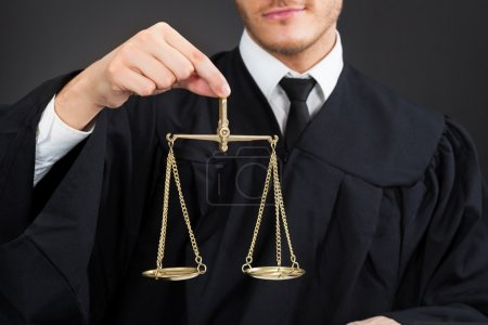 Male Judge Holding Weight Scale