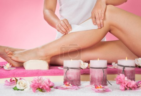 Photo for Midsection of female therapist waxing customer's leg at beauty spa - Royalty Free Image