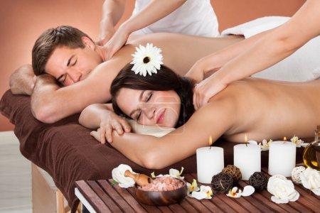 Photo pour Portrait d'épaule récepteur jeune femme massage homme en arrière-plan au spa - image libre de droit
