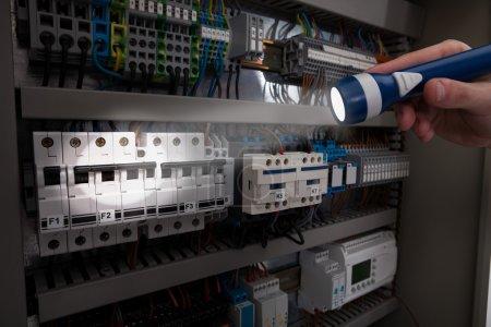 Technician Analyzing Fusebox With Flashlight