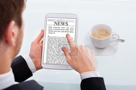 Businessman Reading News On Digital Tablet