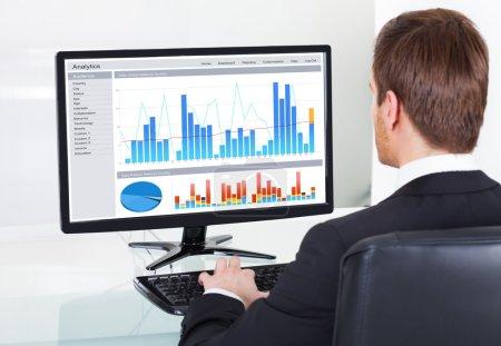 Photo pour Vue arrière du jeune homme d'affaires, analyse des graphiques sur ordinateur au bureau au bureau - image libre de droit