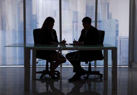 Photo pour Silhouette homme d'affaires et femme d'affaires discuter dans bureau - image libre de droit