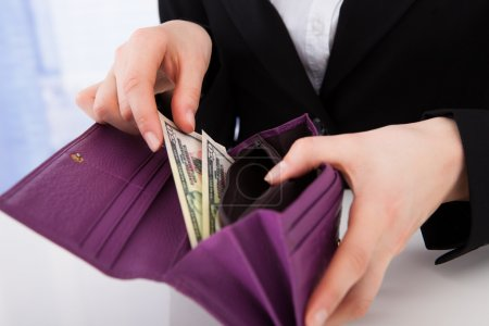 Businesswoman Putting dollars in wallet