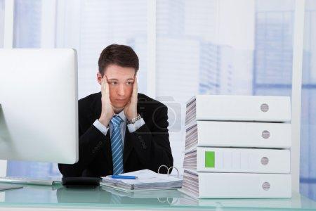 Worried Businessman Looking At Binders