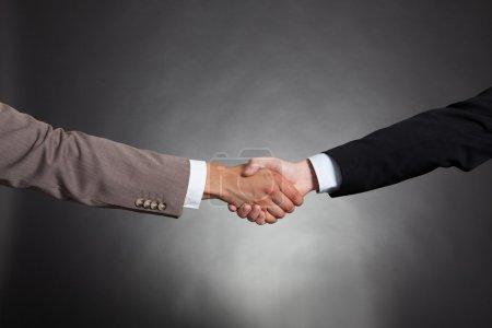Photo pour Image recadrée d'hommes d'affaires se serrant la main sur fond noir - image libre de droit