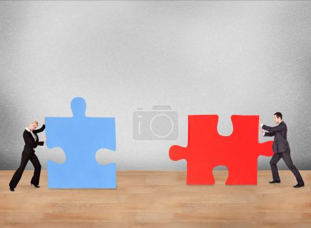 Photo for Business people joining puzzle pieces on desk - Royalty Free Image