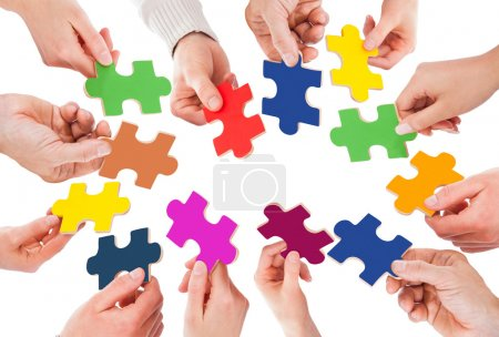 Business People Holding Jigsaw Pieces