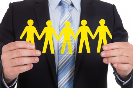 Businessman Holding Team Of Paper People