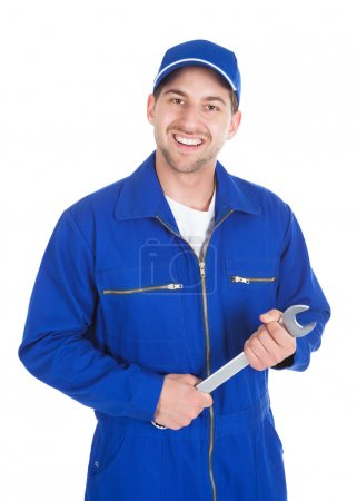 Photo for Portrait of young male mechanic in blue overalls holding spanner over white - Royalty Free Image