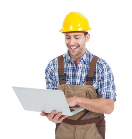 Photo for Smiling young manual worker using laptop over white background - Royalty Free Image