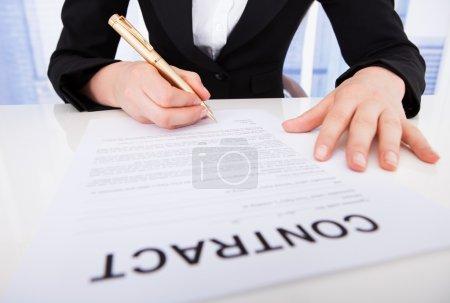 Photo pour Abdomen de la jeune femme d'affaires signature contrat papier au bureau - image libre de droit