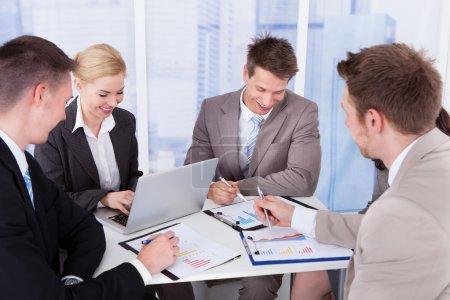 Photo pour Groupe de jeunes gens d'affaires discuter à table dans le Bureau - image libre de droit