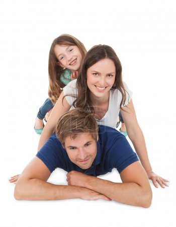Photo for Portrait of playful family piling each other over white background - Royalty Free Image
