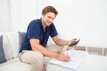 Photo pour Mid homme adulte calcul finances maison à table souriant - image libre de droit