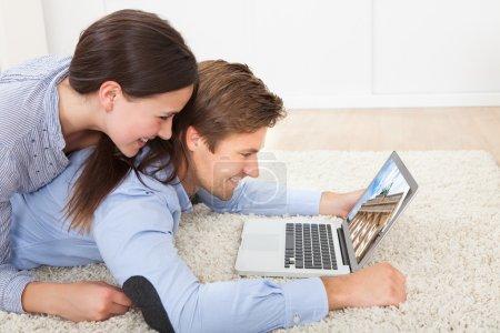 Photo pour Vue latérale du couple regardant la porte de Brandebourg sur un ordinateur portable tout en étant allongé sur un tapis à la maison - image libre de droit