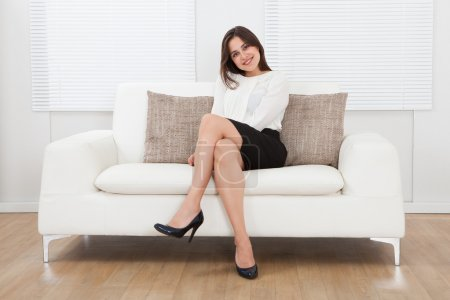Photo for Beautiful young businesswoman sitting on sofa at home - Royalty Free Image