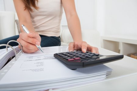 Photo for Midsection of young woman calculating home finances at table - Royalty Free Image