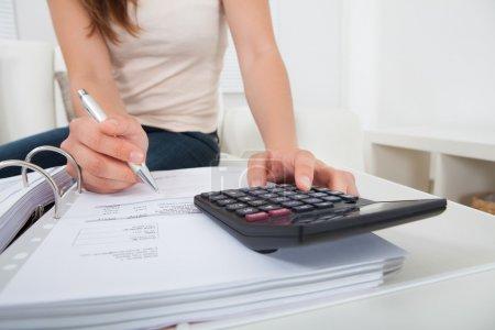 Photo pour Abdomen de la jeune femme calcul finances maison à table - image libre de droit
