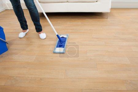 Photo pour Femme de nettoyage plancher de bois franc à la maison - image libre de droit