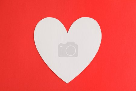 Heart shape paper over red paper background