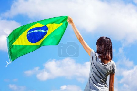 Woman holding a brazil flag