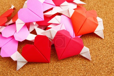 Group of origami colorful heart on corkboard