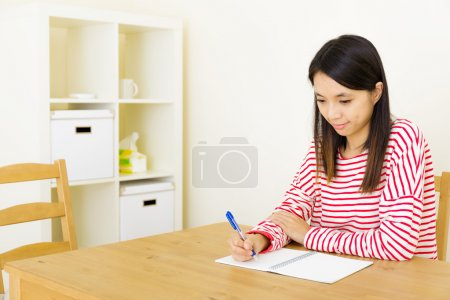 Asian woman writing on notebook