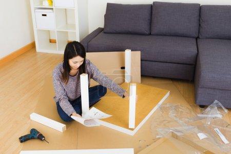 Woman assembling furniture